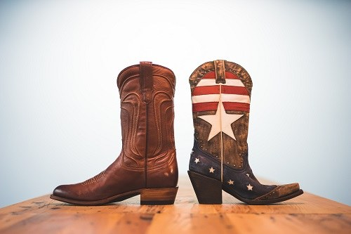 Pair Of Different Cowboy Boots On Table